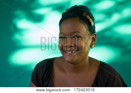 Real Cuban people and emotions portrait of black latina laughing and looking at camera. Happy hispanic young woman from Havana Cuba smiling