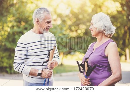 Keeping fit. Positive delighted aged couple holding poles and looking at each other while enjoying their walk in the park