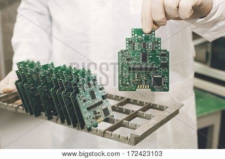Technician with computer circuit board with chips. Spare parts and components for computer equipment. Production of electronics and maintenance. The concept of high technology.