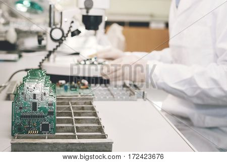 The technician takes a computer board with chips. Spare parts and components for computer equipment. Production of electronics and maintenance. The concept of high technology and robotics.