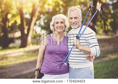 Active way of life. Positive delighted elderly man standing near his wife and hugging her while holding walking poles
