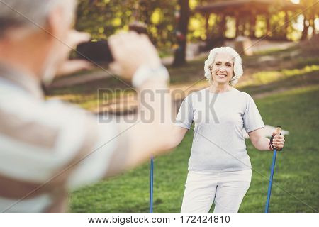 Moment to remember. Cheerful pleasant aged woman holding poles and smiling while posing for a photo