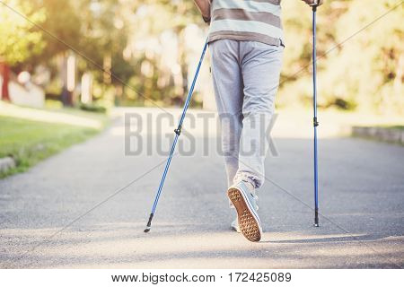 Movement is life. Nice pleasant sporty man holding poles and taking a step while practicing Nordic walking