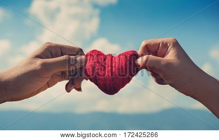 Valentine's concept. Close up couple hands holding red hearts on blue sky background. Copy space.