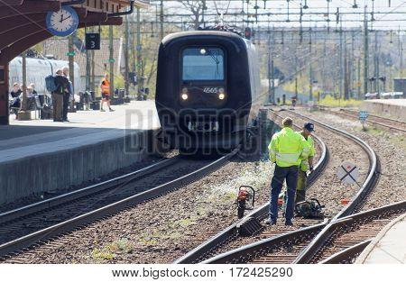 HASSLEHOLM SWEDEN - MAY 05 2016: Tracklayer working with the railroad when a train is arriving to the train station. May 05 2016 Hassleholm Sweden