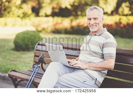 Modern technology. Cheerful good looking man sitting on the bench and using a laptop while working on it