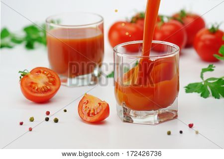 Two glasses of tomato juice with tomatos on white background.