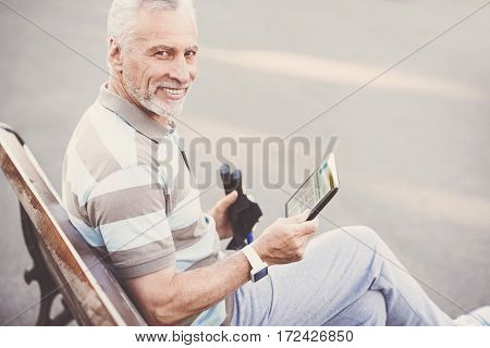 Reading the news. Pleasant joyful elderly man holding an ereader and reading some articles while resting on the bench
