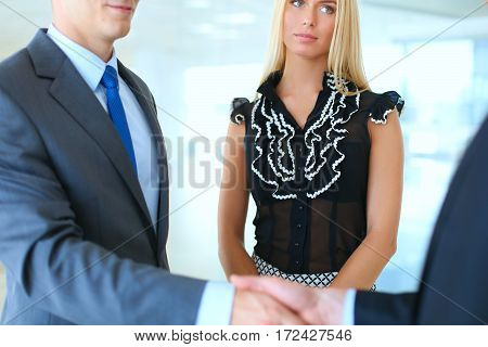 Business people shaking hands after meeting in office .