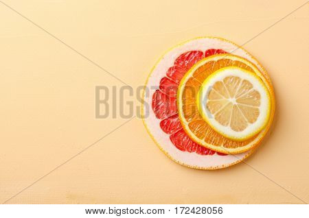 Citrus fruit slices of lemon, orange, grapefruit on yellow background, horizontal, copy space