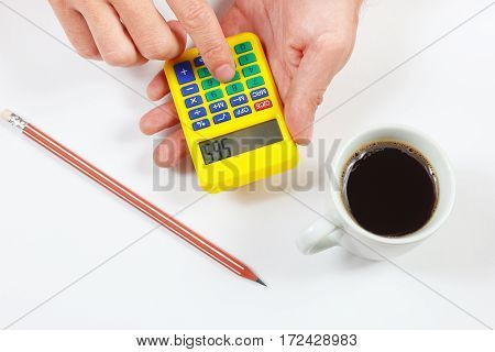 Hands calculate using a pocket calculator on a white background