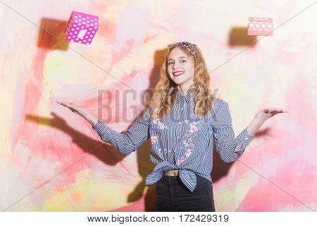 Cheerful pretty girl or beautiful woman with blond hair in blue striped shirt and stylish headband throws two red and pink polkadot gift boxes on colorful wall on abstract background