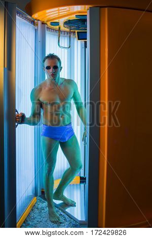 muscular man with sexy healthy body standing in solarium spa salon in blue pants and sunglasses has strong muscle on chest belly and torso