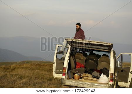Bearded man hipster traveler with moustache in hat travels by minibus and enjoys summer vacation on mountain top on foggy sky