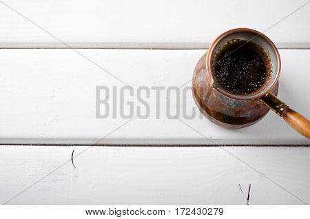 Old copper coffee pot with fresh brewed coffee on white wooden background, horizontal, top view, copy space