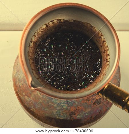 Old copper coffee pot with fresh brewed coffee on white wooden background, square, top view, toned