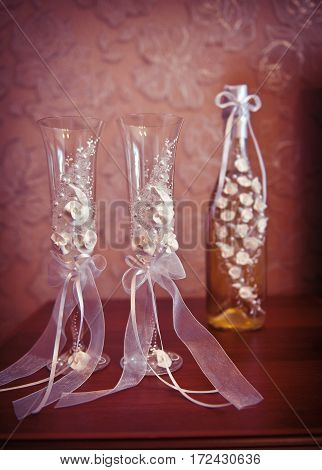 Two wedding glasses and a bottle of champagne on the table.