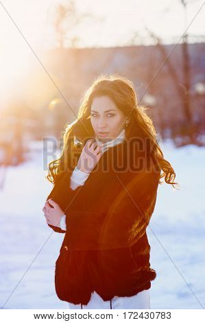 beautiful young woman in a fur coat walks in the winter street.