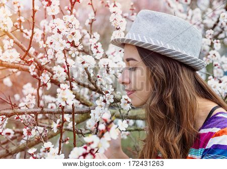 Young woman with hat smelling the cherry blossom in the spring garden