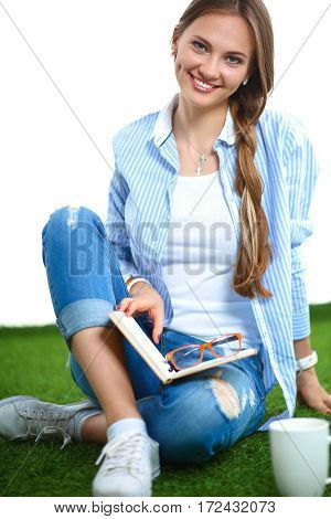 Young woman sitting with book on grass.