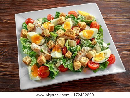 Fresh healthy Caesar salad with chicken, eggs, tomatoes, Cheese and Croutons on white plate.