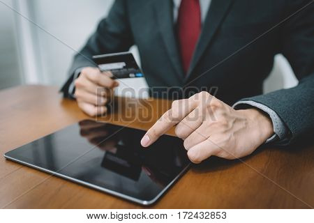 Businessman hand using tablet and credit card. Fintech concept.