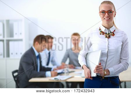 Portrait of a young woman working at office standing .