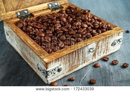 Coffe beans in open old wooden white chest.