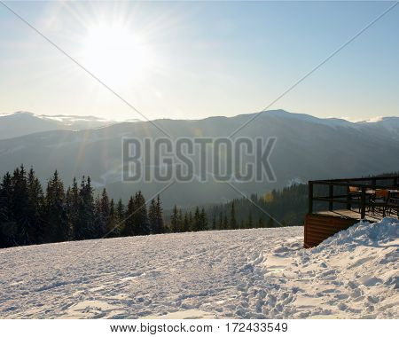 Beautiful fir trees covered with snow andterrace cafe on the background of sunlit mountains Carpathians, Bukovel