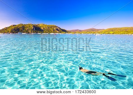 Young attractive man snorkeling in green lagoon in Santa Giulia sandy beach on the south part of Corsica France Europe