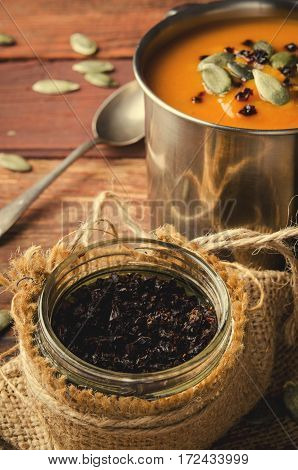 Roasted pumpkin soup in metal mug with seeds and smoked paprika, on rustic wooden background. Vertical, toned
