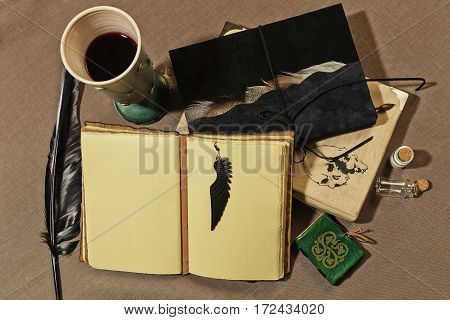 Working place of ancient writer with a cup of wine old books quill and other mystic accessories