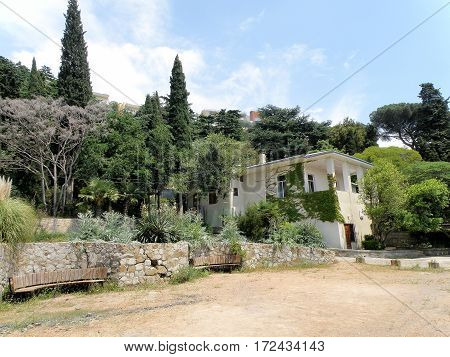 The house is situated in a picturesque location and is surrounded by dense vegetation.