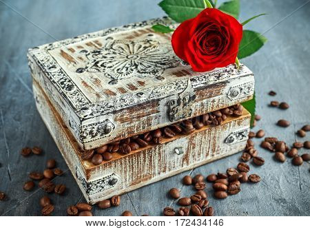 Coffe beans in old wooden chest with crimson red rose on top.