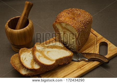 Simple still life from village kitchen - marble bread in eastern european style wooden mortar and an old rural knife
