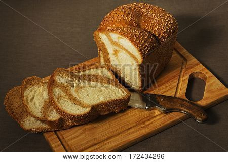 Marble bread loaf and three slices on the old cutting board