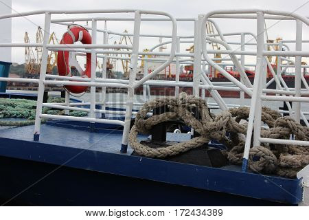 Blue boat deck with white fence, red life ring and thick jute rope. Boat deck details close up view. Jute rope knots on boat deck with seaport view background.