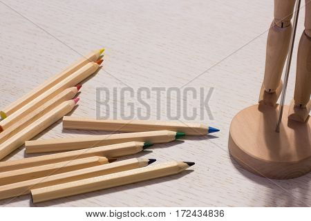 colorful pencils on a table with puppet