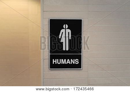 Gender neutral restroom sign that says, HUMANS.