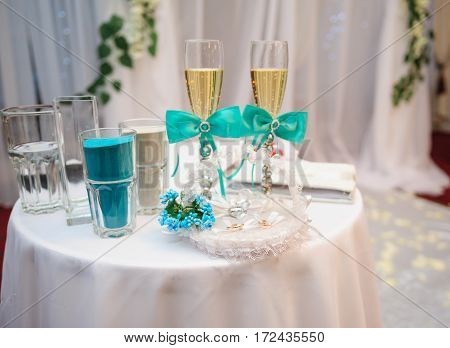 two glasses with champagne and other attributes for the wedding ceremony.