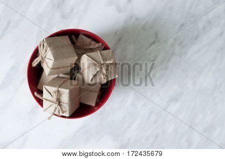 Gift boxes in red bucket on white marble background Christmas and New Year concept. copy space.