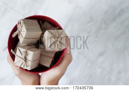 Woman hands holding gift boxes in red bucket on white marble background Christmas and New Year concept. copy space.