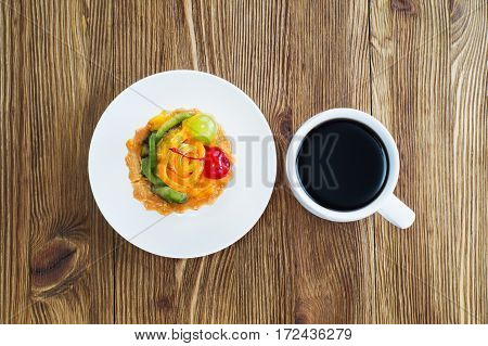 Appetizing cake basket with sliced fruit berries and cup of coffee on rustic wooden background with copy space. Delicious and fresh dessert and coffee top view flat lay. Morning choice.