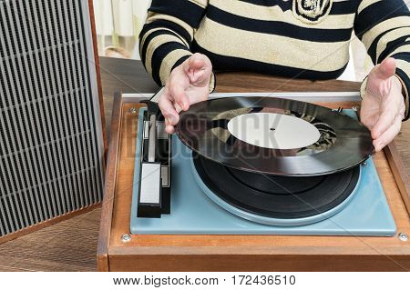 Old woman sitting at a table puts vinyl record on retro player, close-up