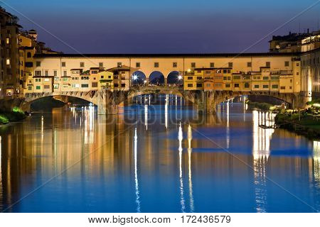 Ponte Vecchio, the old bridge in Florence, Italy. This bridge is famous for the gold and silver jewelers selling their wares across the bridge. Evening photo with reflections on the Arnot River.