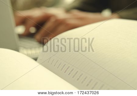 Open notepad with schedule on work-table and working man on background, horizontal, toned