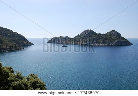 Landscape with a small green island and pleasure boat in the calm blue lagoon in the Aegean Sea in Turkey.