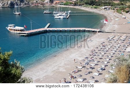 Ciftlik, Turkey - May 30, 2009: View of the beach, blue lagoon with clear water and a pier with pleasure boats on the coast of the Aegean Sea in Turkey.