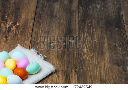 Colorful Easter eggs on vintage towel on old wooden table, rustic background, holiday concept. Textspace, copyspace.