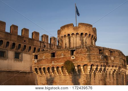 Turrets of Castle San Angelo, alongside the Tiber River in Rome, Italy. Golden late afternoon lighting.